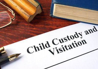 Child Custody and Visitation written on a paper and a book.